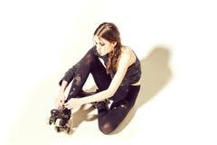 Menina bonita em um assento preto com rolos e laço imagens de stock royalty free