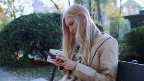 Menina bonita em um banco em seu telefone que olha fotos Parque fresco do outono luz solar macia filme