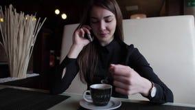 Menina bonita em um café que fala no telefone e no café bebendo video estoque