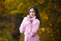 Menina bonita em um casaco de pele cor-de-rosa Fotos de Stock