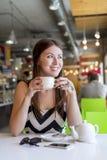 A menina bonita em um chá bebendo do café, café, toma o café da manhã o restaurante que olha para fora na rua Imagem de Stock Royalty Free