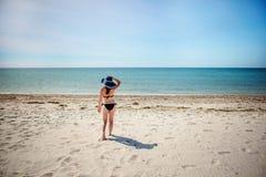Menina bonita em um chapéu azul, andando ao longo da praia foto de stock