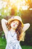 Menina bonita em um chapéu de palha, dado forma seus bordos para um beijo Fotos de Stock Royalty Free