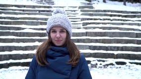 A menina bonita em um chapéu e na roupa do inverno sorrir quando olhares na câmera e apreciar o bom tempo Emoção positiva novo vídeos de arquivo