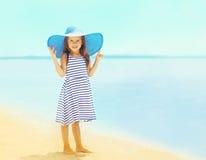 Menina bonita em um chapéu listrado do vestido e de palha do verão que relaxa na praia perto do mar imagem de stock royalty free