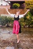 Menina bonita em um dirndl que levanta em um córrego Fotos de Stock Royalty Free