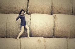 menina bonita em um fundo do monte de feno Foto de Stock