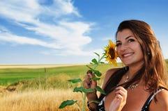 Menina bonita em um girassol da terra arrendada do campo Fotografia de Stock