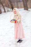 Menina bonita em um lenço do russo com os ovos coloridos para o feriado da Páscoa Foto de Stock Royalty Free