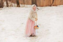 Menina bonita em um lenço do russo com os ovos coloridos para o feriado da Páscoa Fotografia de Stock Royalty Free