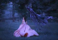 A menina bonita em um longo, rosa, vestido de vibração corre longe da morte sob a forma de um demônio escuro que saia do inferno imagens de stock