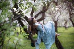 Menina bonita em um pomar de Apple de florescência Foto de Stock