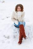A menina bonita sorri na câmera, sentando-se na neve Foto de Stock Royalty Free