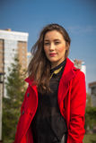Menina bonita em um revestimento vermelho em um fundo das casas fotografia de stock royalty free