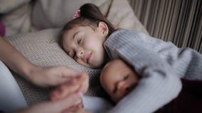 A menina bonita em um sofá cai adormecido e abraçando uma boneca Cursos da mamã uma filha sonolento vídeos de arquivo