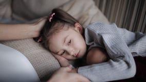 A menina bonita em um sofá cai adormecido e abraçando uma boneca Cursos da mamã uma filha sonolento filme