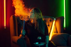 A menina bonita em um t-shirt preto está fumando um cachimbo de água que expira um fumo em um clube noturno luxuoso foto de stock royalty free