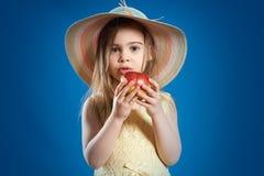 Menina bonita em um vestido amarelo que come uma maçã vermelha deliciosa Imagem de Stock