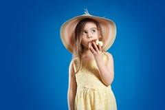 Menina bonita em um vestido amarelo que come uma maçã vermelha deliciosa Foto de Stock