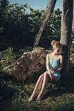 Menina bonita em um vestido azul, levantando o assento na máscara das palmeiras Imagem de Stock
