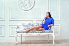 Menina bonita em um vestido azul que encontra-se em um sofá em um branco em um g Imagens de Stock