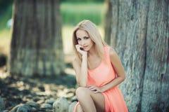 Menina bonita em um vestido cor-de-rosa na floresta foto de stock royalty free
