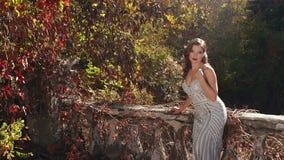 A menina bonita em um vestido de nivelamento anda em um parque abandonado velho no outono video estoque