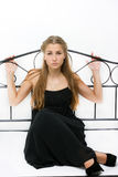 Menina bonita em um vestido e em sapatas em uma cama Imagens de Stock Royalty Free