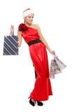 Menina bonita em um vestido e em um chapéu vermelhos de Santa Claus imagens de stock