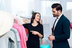 A menina bonita em um vestido e um homem atrativo no terno estão comprando Estão em uma sala de exposições clara foto de stock