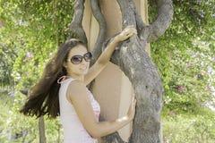 Menina bonita em um vestido e nos óculos de sol que estão ao lado de uma árvore no parque Fotografia de Stock Royalty Free