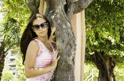 Menina bonita em um vestido e nos óculos de sol que estão ao lado de uma árvore no parque Imagem de Stock Royalty Free