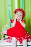 Menina bonita em um vestido vermelho com um descanso vermelho do coração Foto de Stock Royalty Free
