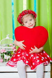 Menina bonita em um vestido vermelho com um descanso vermelho do coração Imagens de Stock Royalty Free
