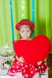Menina bonita em um vestido vermelho com um descanso vermelho do coração Fotos de Stock