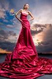 Menina bonita em um vestido vermelho longo fotos de stock royalty free