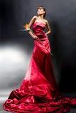 A menina bonita em um vestido vermelho prende a flor exótica foto de stock royalty free