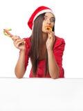 Menina bonita em um vestido vermelho que come o bastão de doces Imagens de Stock Royalty Free