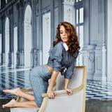 Menina bonita em uma camisa listrada e em uma saia apertada que sentam-se na A.A. fotos de stock