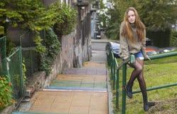Menina bonita em uma camiseta que senta-se em escadas de uma rua dos trilhos imagens de stock