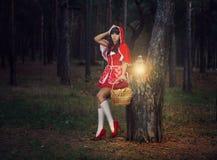 Menina bonita em uma capa de chuva vermelha apenas nas madeiras. Imagens de Stock