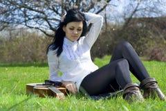A menina bonita em uma grama com uma guitarra Foto de Stock