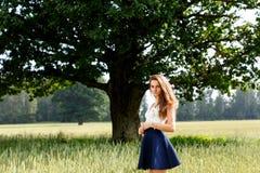 Menina bonita em uma posição do campo fotografia de stock royalty free