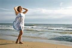 A menina bonita em uma praia do mar toca em um cabelo pelo ha Imagens de Stock