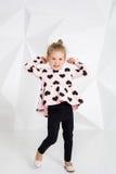 Menina bonita em uma túnica cor-de-rosa com corações pretos e as caneleiras que levantam na frente da câmera no estúdio Imagem de Stock