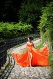 Menina bonita em vestido alaranjado de vibração surpreendente imagem de stock
