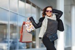 A menina bonita em vidros de sol está guardando sacos de compras, está olhando a câmera e está sorrindo ao estar fora Imagens de Stock Royalty Free