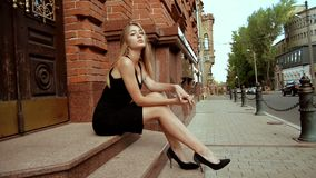 A menina bonita encantador em sapatas e no vestido pretos senta-se fora video estoque