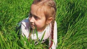 A menina bonita encontra-se em um campo Retrato de uma crian?a feliz Menina na grama verde video estoque