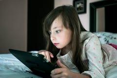 A menina bonita encontra-se em uma cama e em jogar o jogo de computador Fotografia de Stock Royalty Free